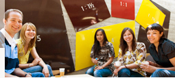 A group of smiling students sitting in front of an artfully designed wall in the Library Building.